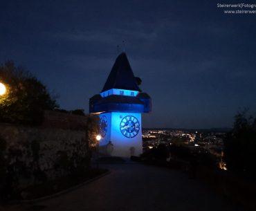 Uhrturm gelb blau beleuchtet